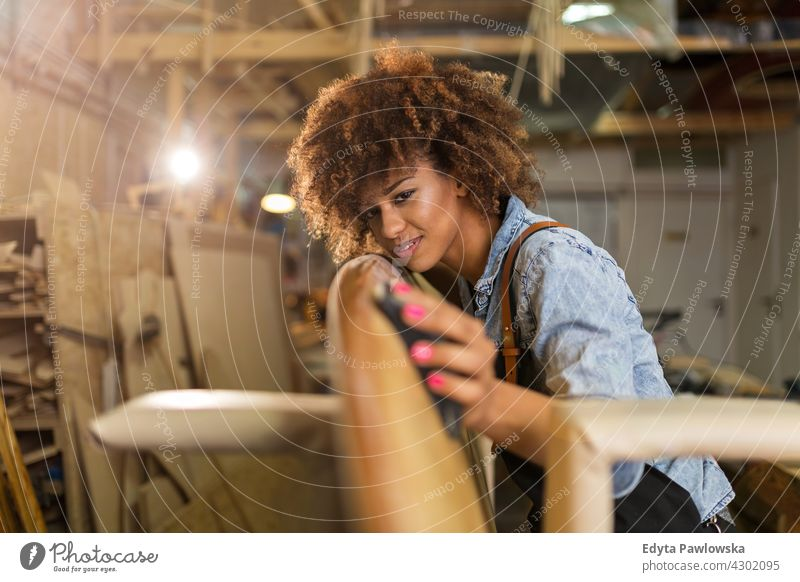 Young woman working on surfboard in her workshop female owner profession service small business employee technician workplace manual worker maintenance adult