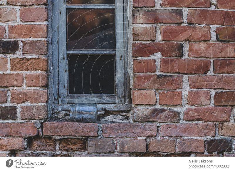 One glass window on old red brick wall. Vintage window in white wooden frame on red brick wall of industrial building. Jar of glass lying on windowsill. jar