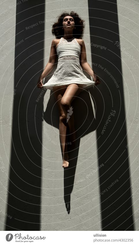young sexy woman lies between two black shadow stripes on the floor in the sun and casts a strong shadow Woman dress dark white mysterious mystery light glamour