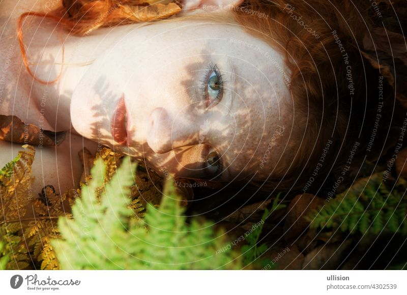portrait of a beautiful natural sexy redheaded woman on the forest floor with the shadow of a fern leaf on her face leaves princess garden elf femininity myth