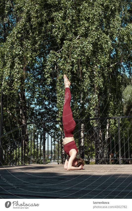 Young brunette woman practicing Salamba Sirsasana Headstand pose in the park on wooden platform Headstand. yoga balance outdoors yogini sport athletic female