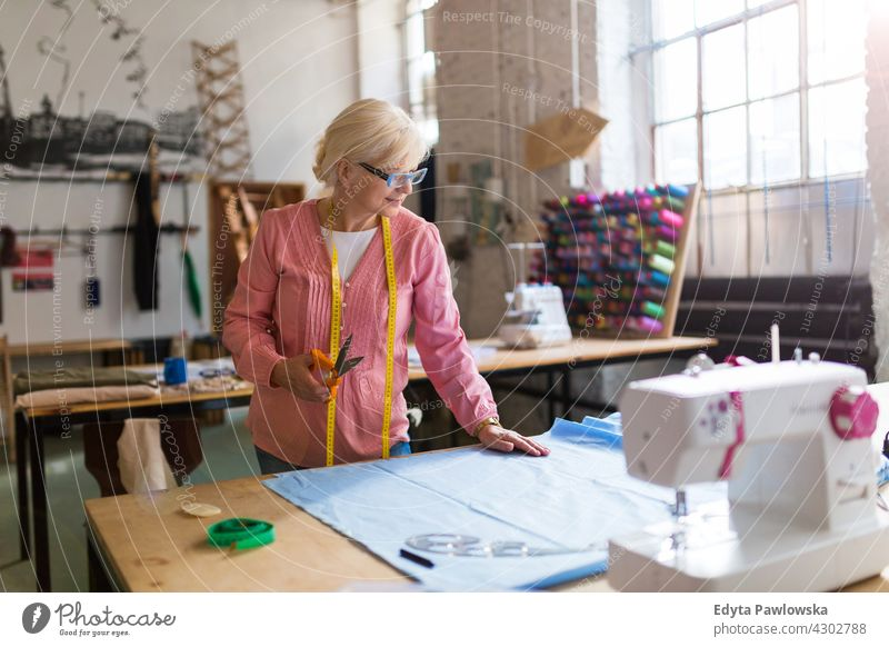 Senior fashion designer  in her workshop Sewing Machine Cloth Fabric Material dressmaker seamstress tailor clothing indoors woman female mechanic owner