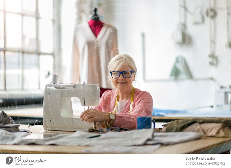 Senior fashion designer using a sewing machine in her workshop Sewing Machine Cloth Fabric Material dressmaker seamstress tailor clothing indoors woman female