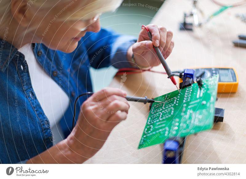 Senior woman in electronics workshop measurement current electricity Electrician Engineer Equipment Expertise Industry Job Repair soldering iron indoors female
