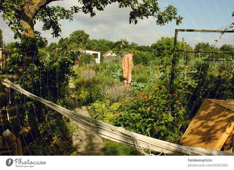 Young woman standing in the middle of her flower and vegetable garden Woman Garden self-sufficiency do gardening Relaxation Garden plot allotment Biological