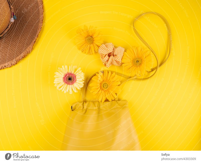 Yellow fashion lady shoulder bag with gerbera daisy flowers on monochrome background yellow handbag shopping accessory color hat straw vacation holiday woman