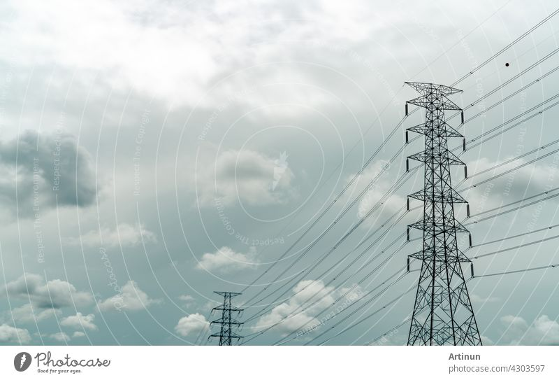 High voltage electric pylon and electrical wire with grey sky and white clouds. Electricity poles. Power and energy concept. High voltage grid tower with wire cable. Infrastructure. Power distribution
