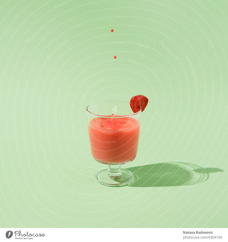 Summer strawberry juice with falling drops isolated on a green background. summer Abstract minimal freshness Contemporary Square aesthetic art beverage cocktail