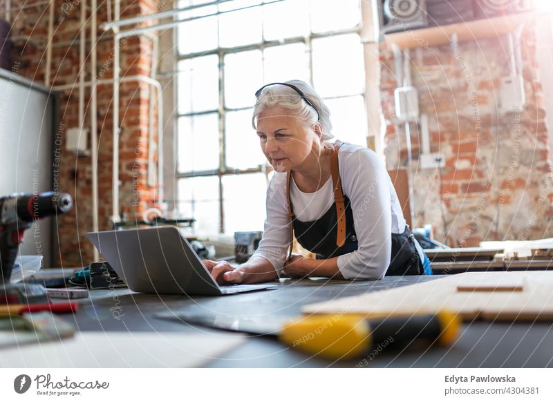 Senior woman using laptop in her workshop indoors female mechanic owner profession service small business employee working technician workplace manual worker