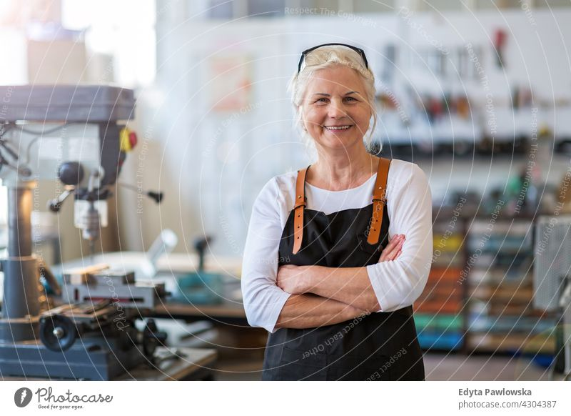 Senior craftswoman in her workshop indoors female mechanic owner profession service small business employee working technician workplace manual worker