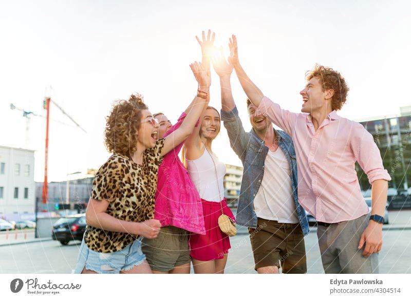 Friends joining hands Group Group of people together woman women young casual beautiful attractive girls male female friends friendship smiling happiness happy
