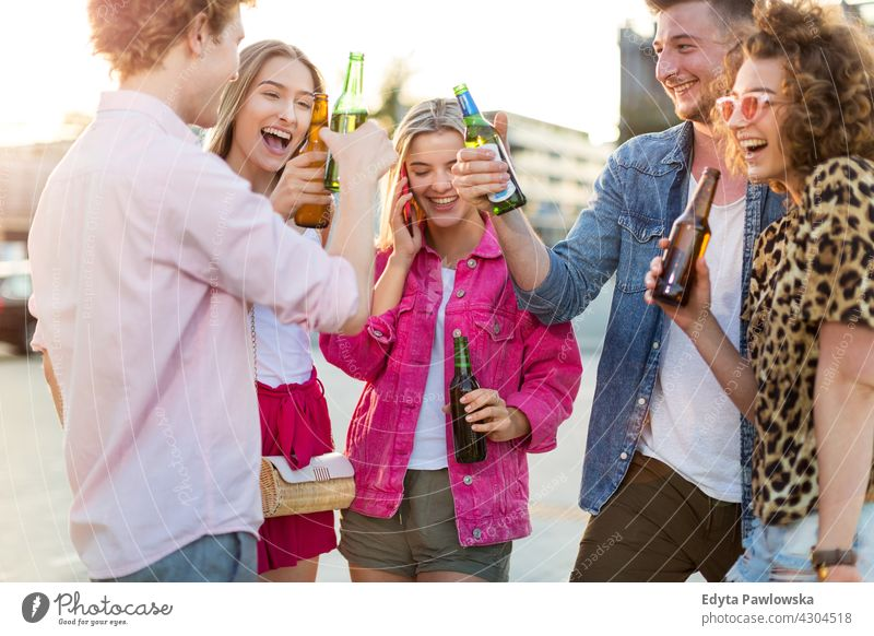 Group of friends drinking beer together Group of people woman women young casual beautiful attractive girls male female friendship smiling happiness happy