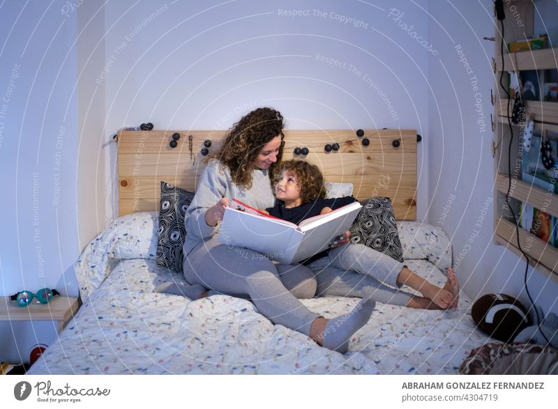 young woman reading a story to her son lying in bed mother child hispanic two book person boy family happy indoor female home happiness kid childhood lifestyle
