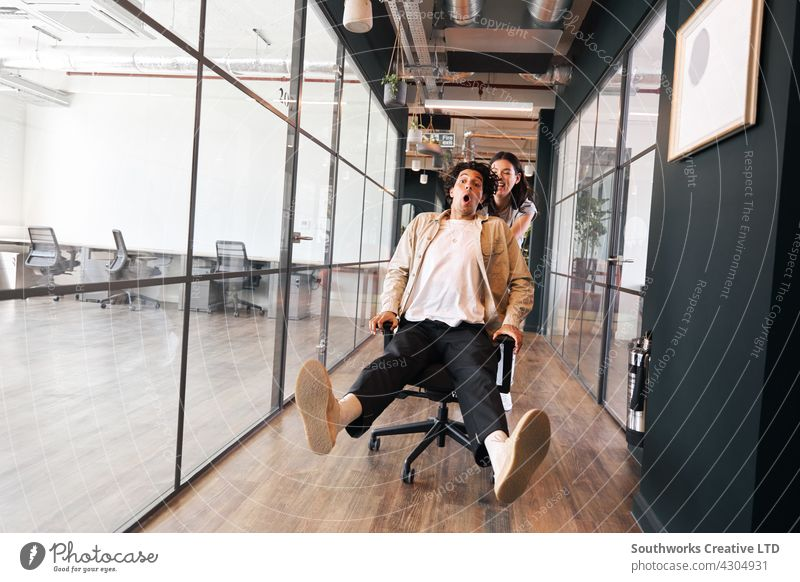 Young woman having fun pushing man on chair along walkway in open plan office young laughing friday feeling monday blues celebrating excitement informal casual