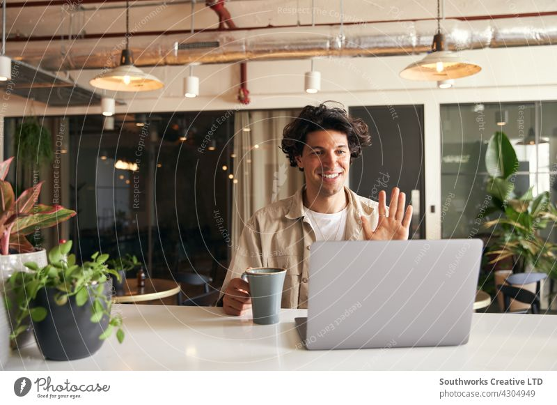 Young man remote working in coffee shop hosting virtual meeting via video call on laptop young cafe video chat flexible working start up creative designer coder