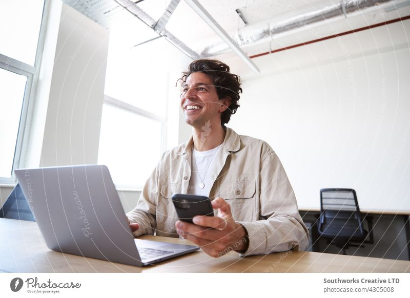 Young man with laptop and mobile phone at desk working on start-up company in open plan office Man youthful Office Desk Telephone Mobile cell review