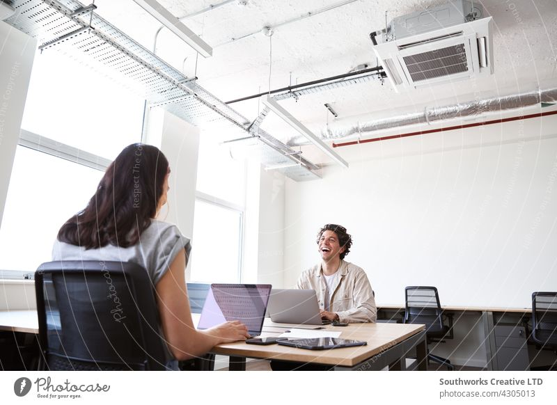 Young couple with laptops at desks working on start up business in rented open plan office space woman young meeting informal casual talking modern co-working