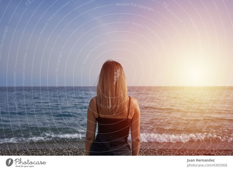 woman looking at the horizon in the sea. young beach sunset relaxation freedom carefree horizontal enjoy enjoyment standing young adult back one person alone