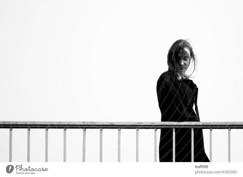 the young woman walks over a bridge and looks down Long-haired Looking away Fashion 18 - 30 years Hair and hairstyles Feminine Lifestyle Beauty Photography