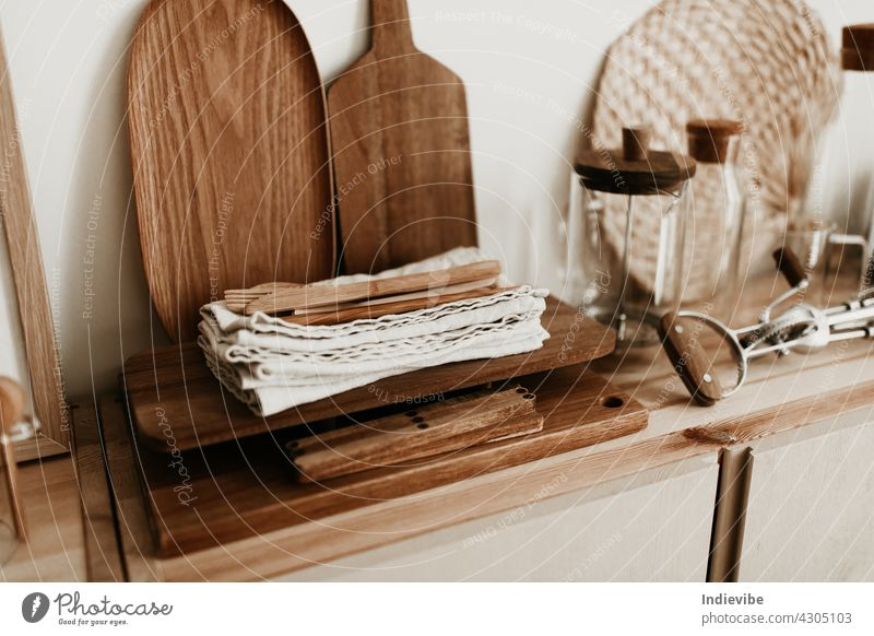 Wooden cutlery and linen napkins on dark brown chopping board. A wooden tray and chopping board in the background with a few glass jar. light shelf cupboard