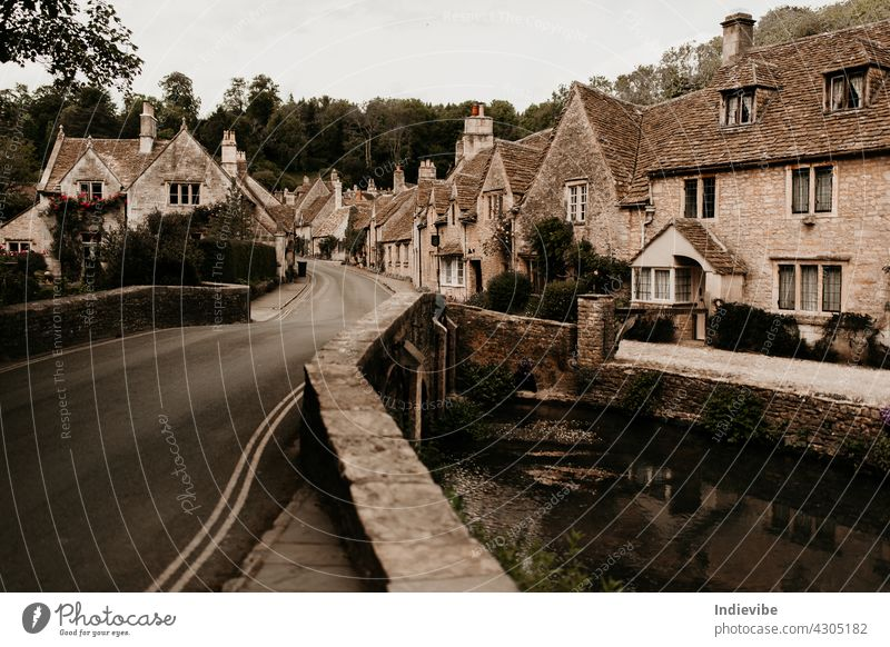 Castle Combe traditional English village with pretty bridge on a summer day. Nobody and no car on the street. architecture building castle city classic combe