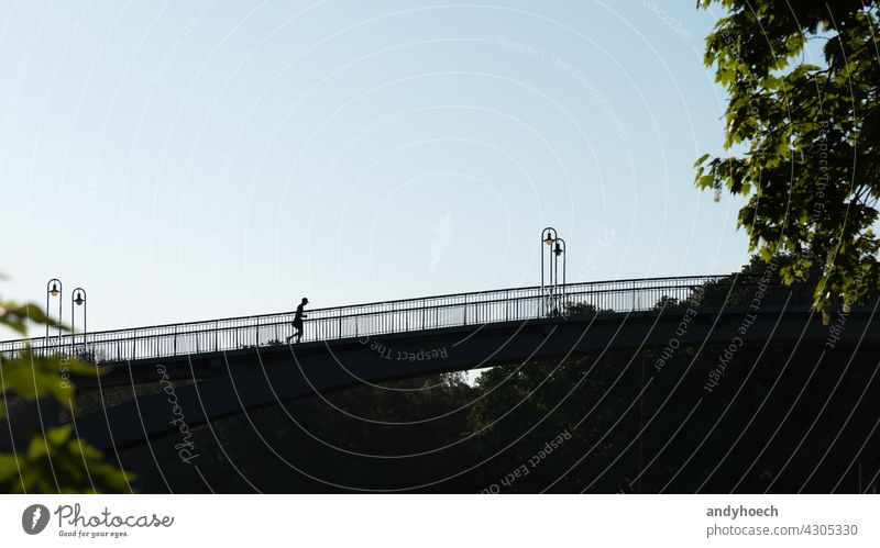 Silhouette of a joggers on a bridge action active activity adult athlete athletes athletic athletics Background backlit competition copy space endurance energy