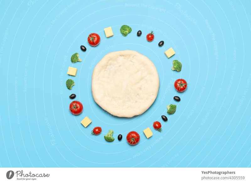 Vegan pizza ingredients, top view. Raw pizza dough and vegetables on blue table above aligned alternative arranged background bake broccoli cashew cheese color