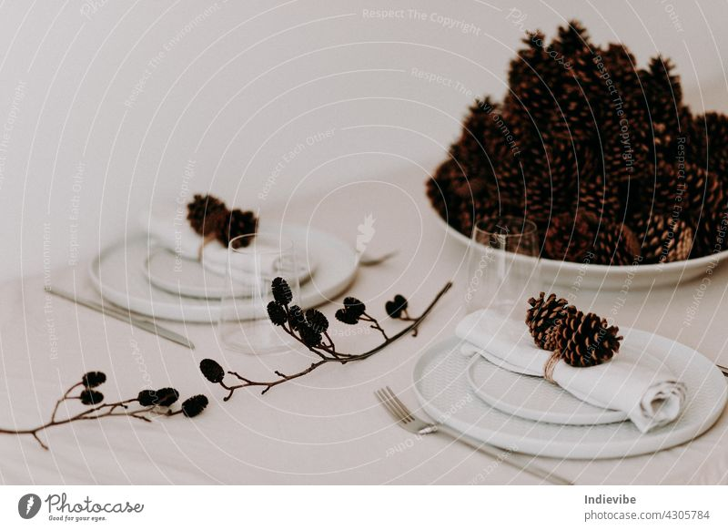 A big bowl of pine cones on a Christmas dinner table with plates and glasses for stylish holiday decoration christmas meal cutlery family supper food festive