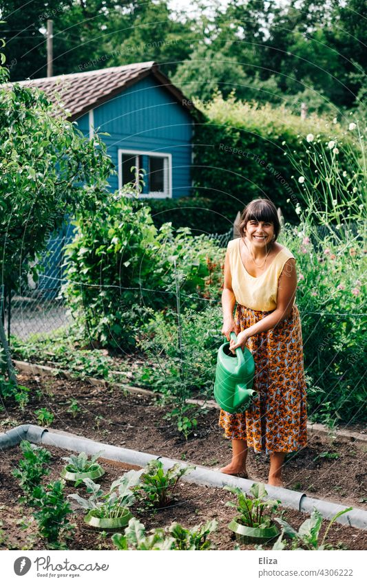 Woman watering the vegetable beds in the allotment garden with a watering can Garden Cast Gardening Watering can Nature Summer gardener variegated cheerful