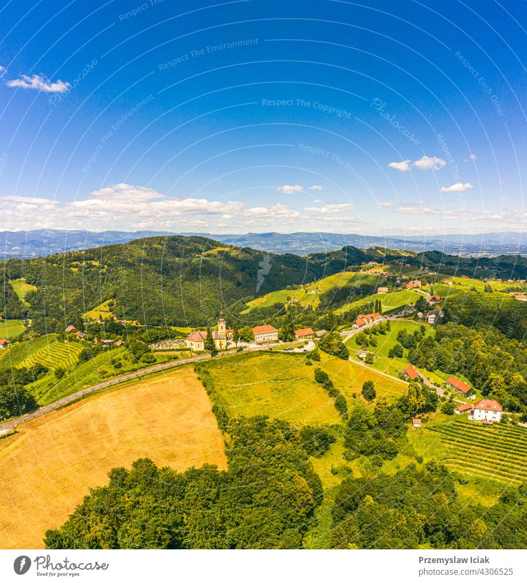 Aerial view of green hills and vineyards with mountains in background. Austria vineyards landscape in Kitzeck im Sausal summer wine nature spring agriculture
