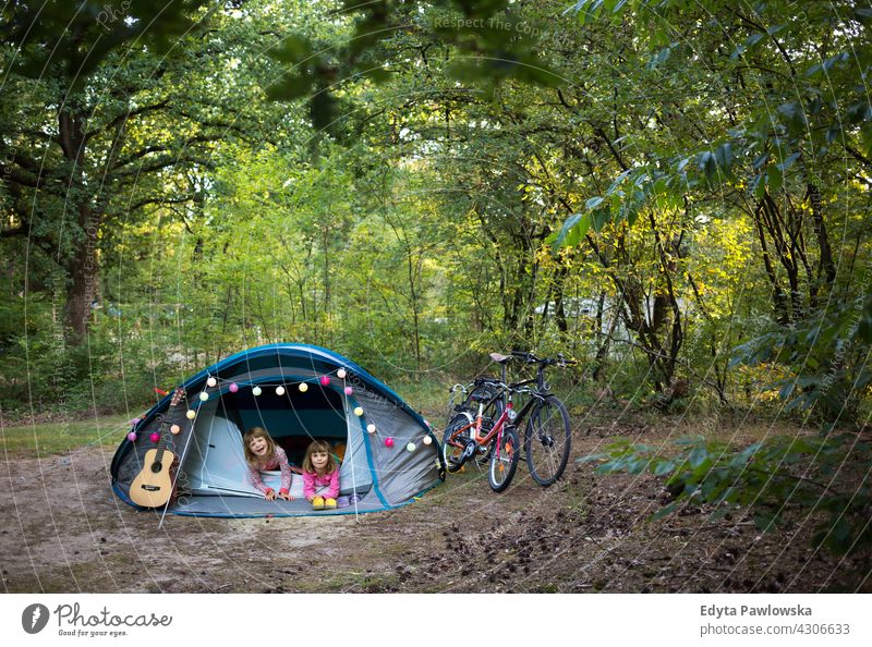 First Time Camping hiking cycling vacation holiday bike bicycle tent forest children kids family camping happy smiling night evening sleeping trek trekking
