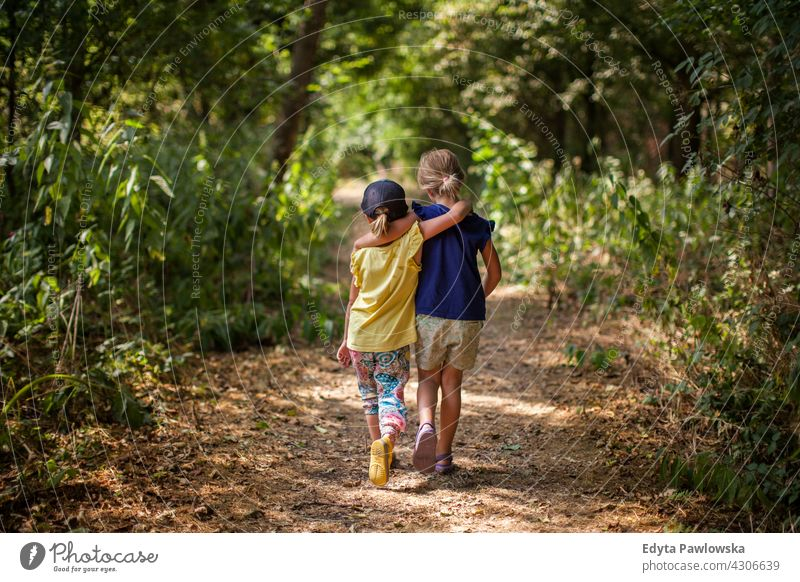 Young children walking in forest friends together hugging sisters summer nature happy outdoor lifestyle sunny activity happiness young leisure girl family