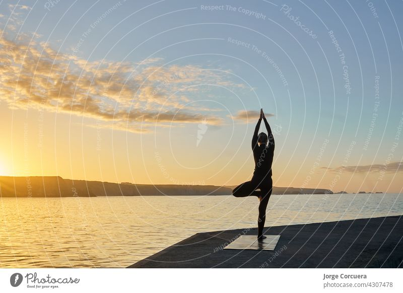 silhouette of woman practicing yoga in backlight young fitness slim workout exercise pose lifestyle caucasian female position training healthy activity person