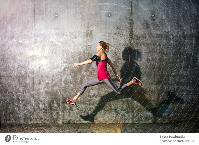 Young woman jumping against grey wall leaping action healthy dance exercise flexibility Jogger runner jogging running people young female energy clothing
