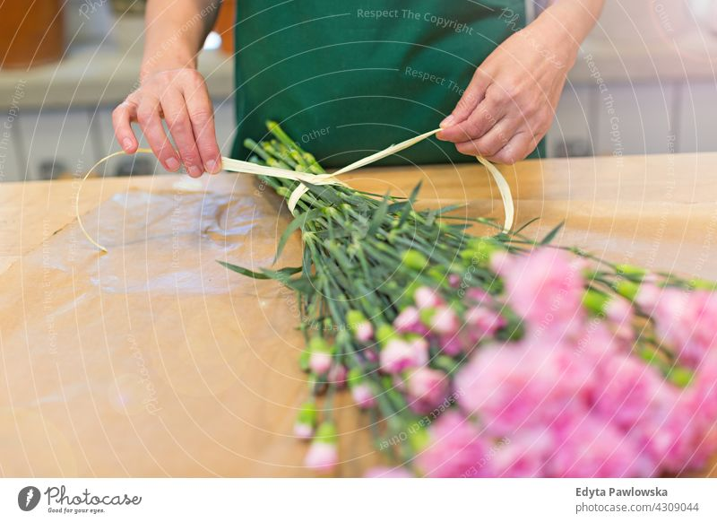 Florist at work flower flowers bunch bouquet holding people senior mature woman female employee working job occupation profession botanist blooming blossoming