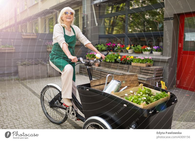 Happy owner of a flower shop using cargo bike bicycle cycling transport commuting delivery Florist people adult senior mature woman female smiling happy apron
