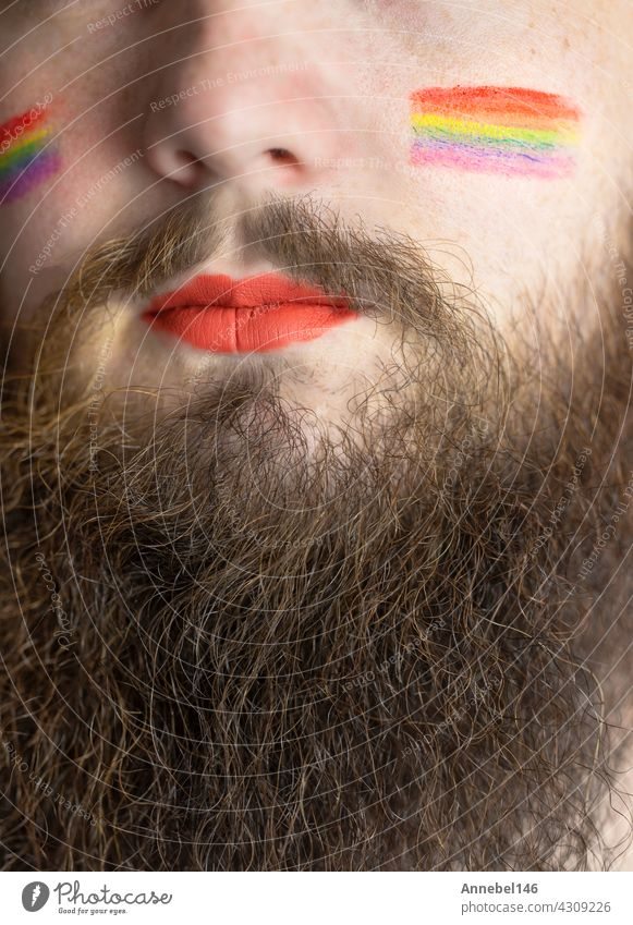 Young handsome bearded man with pride flag on his cheek, rainbow flag standing for LGBTQ, Gender right and sexual minority. Portrait lgbt homosexual equality