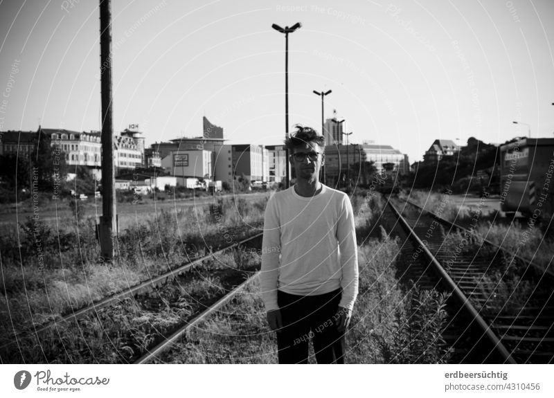 Man standing somewhat lost between disused tracks in front of city backdrop black-white Railroad tracks FALLOW LAND silent overgrown plants lost places Doomed