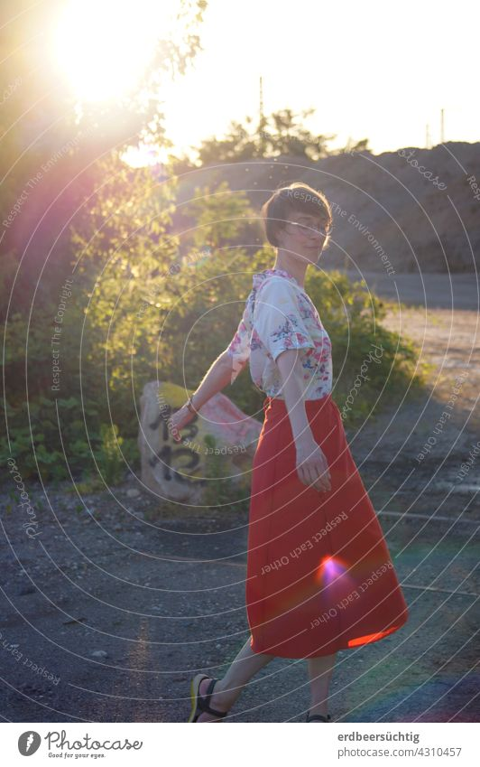 Dancing in the sunlight. Young woman with red skirt dancing on fallow land in the sunlight Woman Elated fortunate Sun Sunlight Back-light FALLOW LAND