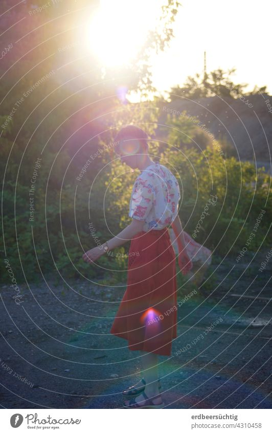 Sundrops keep falling on my head - woman with skirt on fallow and big glare on her head Woman Walking Skirt garments Shirt eyeballed Red Sunlight evening light