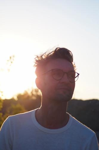 Good humored young man with glasses and two day beard in back light Man Back-light Evening sun portrait Masculine Human being Young man Adults Exterior shot