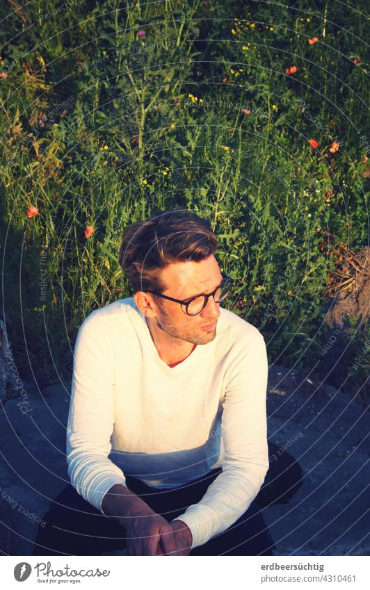 Man squats and waits in the evening light Crouch Wait Eyeglasses Bushes Green Poppy FALLOW LAND Colour photo warm Calm Exterior shot Summer Pastime Boredom