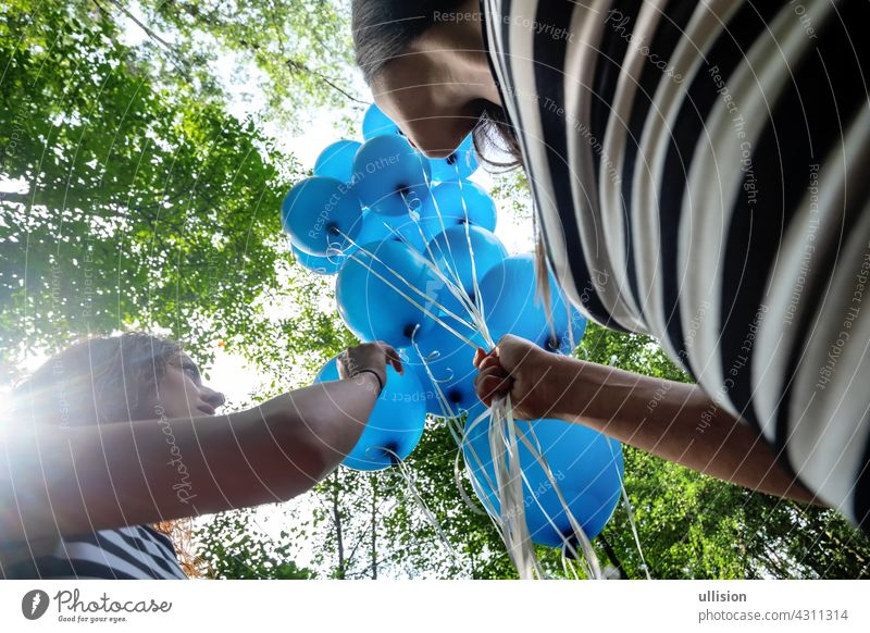 View from below on 2 blond women in black and white striped little ones with a bunch of blue balloons friends people fun beauty female adult fashion summer