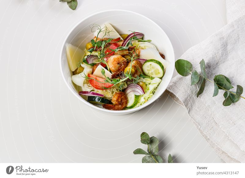 Close-up delicious summer salad with fresh vegetables and seafood on a white background. Seasonal vegetables, shrimp and goat cheese. Healthy Mediterranean natural food. Food photography. Copy space