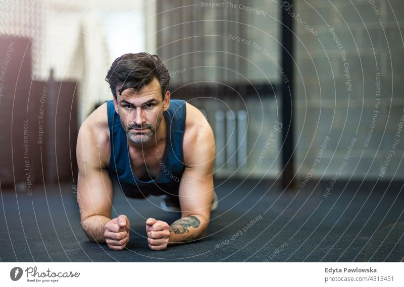 Man working out in gym fitness club health club body healthy sport lifestyle exercise training workout active exercising strength gym clothes sportswear effort