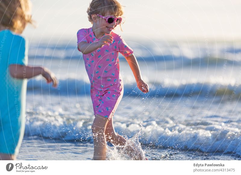 Children playing on the beach young siblings fun family girls children kids New Zealand daytime oceania outdoors scenery travel landscape nature scenic woman