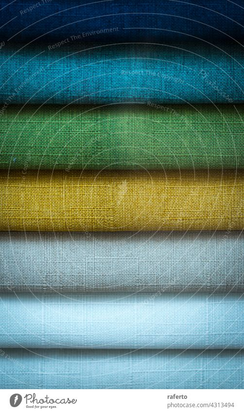 A Stack of some colored fabrics textile stack clothes cotton background fashion material pattern clothing texture blue green yellow folded rainbow pile bright