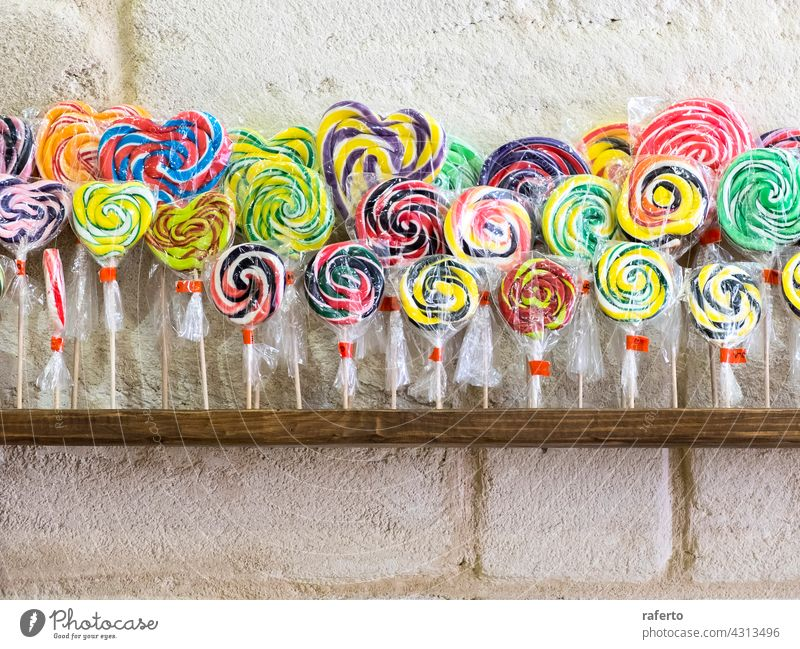 Colorful spiral lollipops on shop shelf swirl candy confectionery sweet colourful striped unhealthy isolated stick sucker red sugar white background delicious
