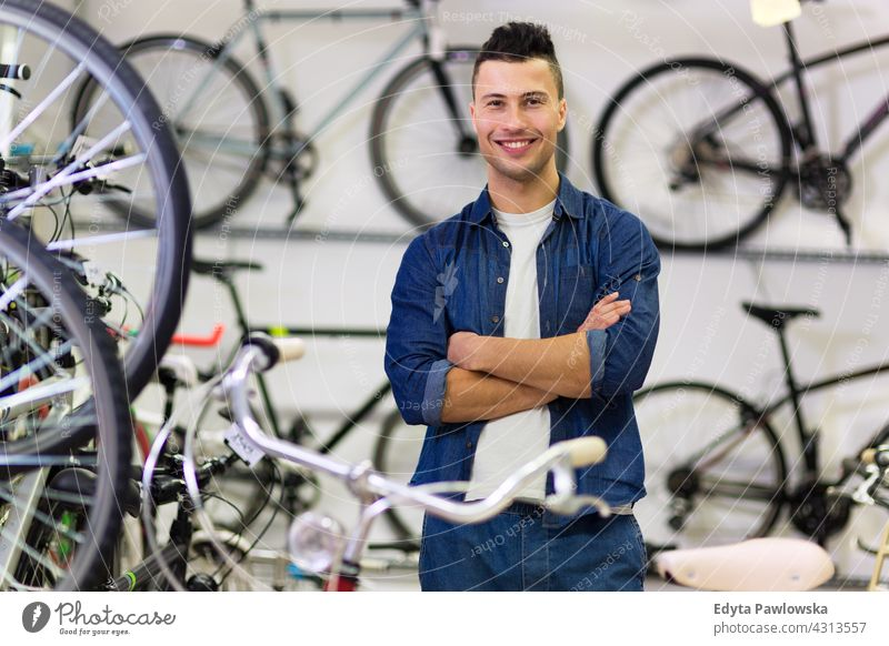 Man working in bike shop assistant bicycle bicycle mechanic bicycling bicyclist biking businessman buying commerce friendly help helpful indoors job manager