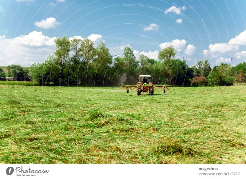 Agriculture - Mowing meadow. Red tractor mowing green pasture. Farmer in a modern tractor on a sunny day. agricultural field Machinery Clouds country Landscape